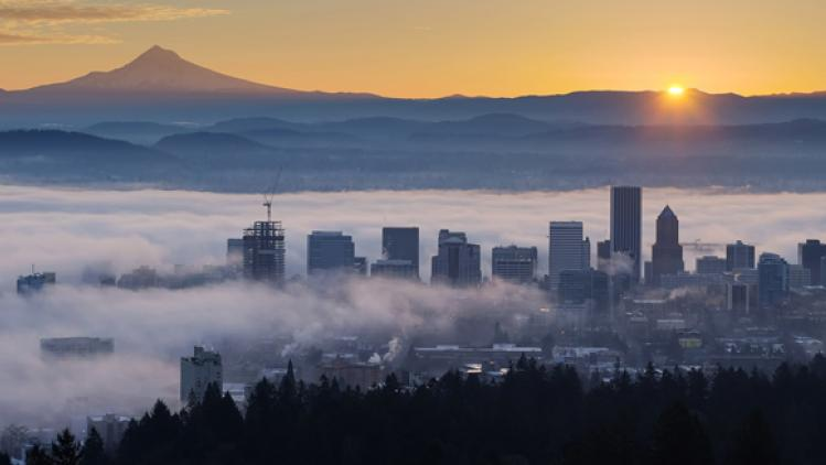 Image of the sun rising over Mt. Hood and showing a foggy Portland, Oregon cityscape